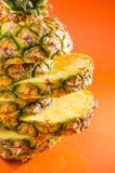 Geschnittene der Nahaufnahme künstlerische, stehende Ananas auf orange Hintergrund, vertikaler Schuss Stockbild