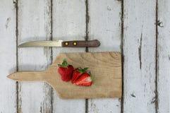 Geschnittene Erdbeere auf einem hölzernen Schreibtisch mit einem Messer Stockfotos