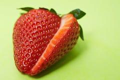 Geschnittene Erdbeere auf grünem Hintergrund Stockfotos
