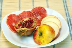 Geschnittene Früchte auf weißem Teller Stockbild
