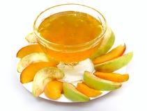 Geschnittene Früchte und Honig Stockfotografie