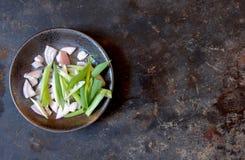 Geschnittene Frühlingszwiebel und Schalotten in einer grauen Schüssel, gelassen von der Mitte, auf einem grauen Hintergrund, Drau stockfoto