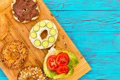 Geschnittene frische Bagel mit köstlichen Zutaten Stockfoto