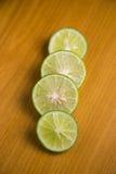 Geschnittene frische grüne Zitrone auf einem braunen hölzernen Hintergrund Stockfotografie