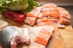 Geschnittene frische Lachse mit Kopfsalat, rotem Pfeffer und Knoblauch Stockbild