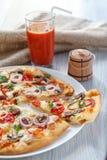 Geschnittene ganze frische Pizza mit Tomaten, Salami, Käse und mushr lizenzfreie stockfotografie