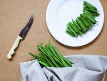 Geschnittene grüne Bohnen auf einer weißen Platte und ein Bündel grüne Bohnen Stockfotografie