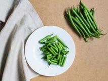 Geschnittene grüne Bohnen auf einer weißen Platte und ein Bündel grüne Bohnen Lizenzfreie Stockbilder
