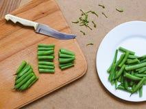 Geschnittene grüne Bohnen auf einer weißen Platte und geschnitten von den grünen Bohnen Stockfotos