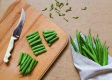 Geschnittene grüne Bohnen und ein Bündel grüne Bohnen auf dem Tisch Lizenzfreie Stockfotos