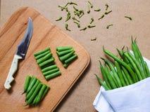 Geschnittene grüne Bohnen und ein Bündel grüne Bohnen auf dem Tisch stockfoto