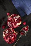 Geschnittene Granatapfel- und Waldfrüchte mit antikem silbernem Löffel Stockfotos