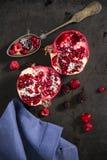 Geschnittene Granatapfel- und Waldfrüchte mit antikem silbernem Löffel Stockbild