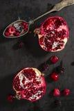 Geschnittene Granatapfel- und Waldfrüchte mit antikem silbernem Löffel Lizenzfreie Stockfotos