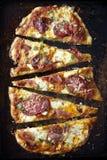 Geschnittene Handwerkerpizza auf einem dunklen Hintergrund Lizenzfreie Stockfotografie