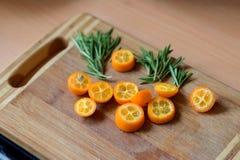 Geschnittene japanische Orange und Basilikum Stockbilder