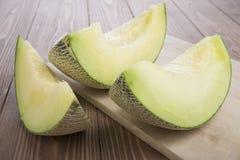geschnittene Kantalupenmelone und volle Melone auf hölzerner Platte und hölzernem Hintergrund Stockfotos