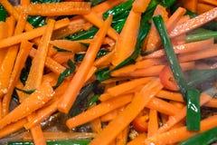 Geschnittene Karotten und Frühlingszwiebeln, die in einer Wanne braten lizenzfreie stockfotografie