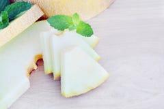 Geschnittene Melone auf einem hölzernen Hintergrund Stockbild