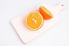 Geschnittene Orange auf Schneidebrett Stockfotos