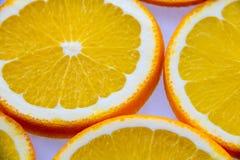 Geschnittene Orangen, die auf einer hellen Oberfläche liegen Lizenzfreie Stockfotos