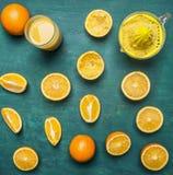 Geschnittene Orangen, ein Juicer, ein Glas Draufsichtabschluß des Hintergrundes des Safts hölzerner rustikaler oben Stockbild