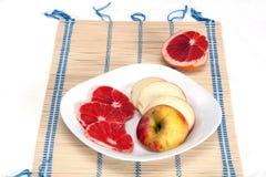 Geschnittene Pampelmuse und Apfel Stockbilder