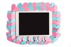 Geschnittene Papierherzen, die Tablet-Computer mit dem leeren Bildschirm lokalisiert auf weißem Hintergrund gestalten lizenzfreie stockbilder