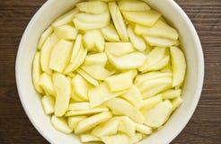 Geschnittene Äpfel im Wasser für einen Apfelkuchen Stockbild