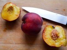 Geschnittene Pfirsiche auf einer hölzernen Platte Stockbilder