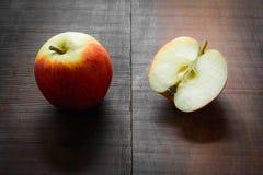 Geschnittene rote Äpfel auf einem rustikalen Holztisch Stockbild