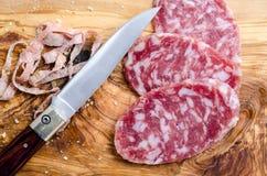 Geschnittene Salami auf einem hölzernen Brett Lizenzfreies Stockfoto