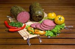 Geschnittene Salami mit Gemüse Stockfotografie