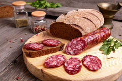 Geschnittene Salami und Brot Stockfotografie