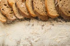 Geschnittene Stücke Brot auf Holztisch mit Mehl Stockbild