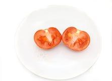 Geschnittene Tomate auf der Platte Lizenzfreie Stockfotos