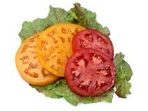 Geschnittene Tomaten auf Kopfsalat Stockfotos