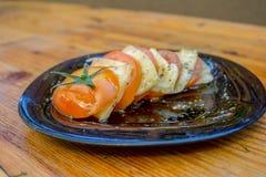Geschnittene Tomatenplatte mit Scheiben des Käses, der Gewürze und des Olivenöls stockfotos