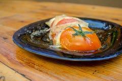 Geschnittene Tomatenplatte mit Scheiben des K?ses, der Gew?rze und des Oliven?ls lizenzfreies stockbild