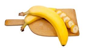 Geschnittene und ganze Bananen auf einem Schneidebrett Lizenzfreies Stockfoto