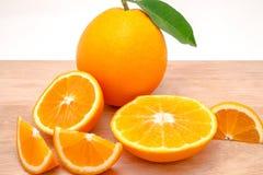 Geschnittene und ganze Orangen auf einem Brett, lokalisiert auf weißem Hintergrund Lizenzfreie Stockfotos