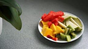 Geschnittene und gewürfelte exotische Früchte dienten auf einer Platte, mit einer Anlage im Hintergrund stockfotografie