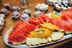 Geschnittene Wassermelone und malon auf einem Holztisch Lizenzfreie Stockfotos