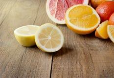 Geschnittene Zitrone auf dem Hintergrund von Zitrusfrüchten auf dem hölzernen ta Lizenzfreie Stockfotos