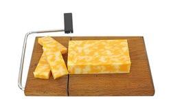 Geschnittener Colby Jack Käse auf Schneidmaschine Stockfotos