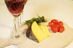 Geschnittener gelber Käse und kleine rote Tomaten stockbilder