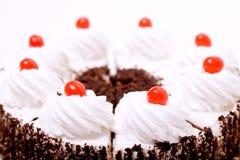 Geschnittener Kuchen mit gepeitschten sahnigen Spitzen Stockfoto