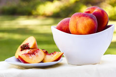 Geschnittener Pfirsich und Schüssel voll Pfirsiche Stockbilder