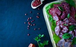 Geschnittener Salamistapel auf hölzernem Brett mit Tomaten und Basilikum verlässt mit Salat auf einem hölzernen schwarzen Hinterg lizenzfreies stockbild