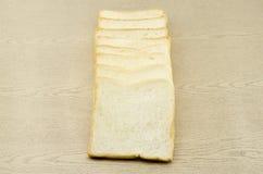 Geschnittenes Brot auf braunem Holz Lizenzfreies Stockfoto